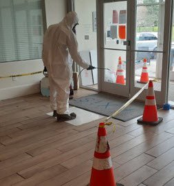worker-disinfecting-entryway